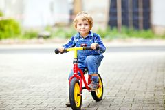 Active blond kid boy in colorful clothes driving balance and learner`s bike or bicycle in domestic garden. Toddler child royalty free stock images