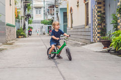Active blond kid boy driving bicycle n the street of the city. Toddler child dreaming and having fun on warm summer day. outdoors. Games for children. Balance Stock Photo