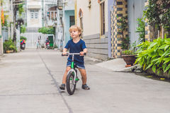 Active blond kid boy driving bicycle n the street of the city. Toddler child dreaming and having fun on warm summer day. outdoors. Games for children. Balance Royalty Free Stock Photo
