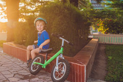Active blond kid boy driving bicycle in the park near the sea. Toddler child dreaming and having fun on warm summer day. outdoors Stock Photography