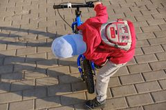 Active blond kid boy driving bicycle in the park. Toddler child dreaming and having fun on warm summer day. Outdoors games for children. Balance bike concept Stock Image