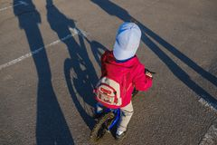 Active blond kid boy driving bicycle in the park. Toddler child dreaming and having fun on warm summer day. Outdoors games for children. Balance bike concept Royalty Free Stock Photos