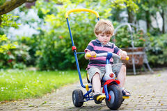 Active blond kid boy driving tricycle or bicycle in domestic gar Stock Photos