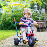 Active blond kid boy driving tricycle or bicycle in domestic gar Stock Photo