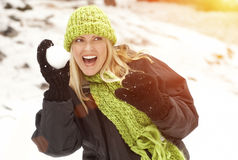 Active Blonde Woman Outdoors Throwing Snowballs in the Wintery Snow Stock Images