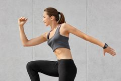 Active bodybuilder girl being photographed in motion, has dark pony tail, does stretching exercises dressed in casual clothes, pos stock image
