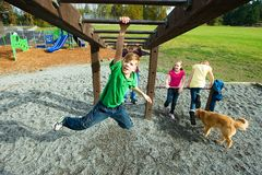 Active boy climbing on playground equipment Stock Photo