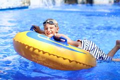 Active boy enjoying water slide in aquapark Royalty Free Stock Image