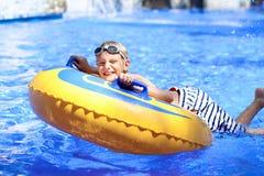 Active boy enjoying water slide in aquapark Royalty Free Stock Image