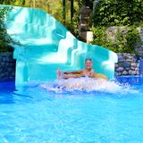 Active boy enjoying water slide in aquapark Stock Photography
