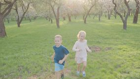 Active boy and girl run near the trees in the park. Beautiful nature. Slow motion.  stock video footage