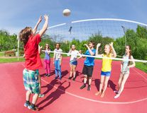 Active boy and girls playing volleyball together Stock Image