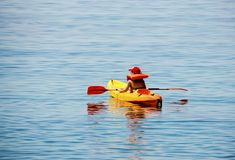 Active  boy, having fun enjoying adventurous experience kayaking on the sea. A sunny day during summer vacation in a greek island Royalty Free Stock Photography