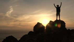 Active boy with open arms in mountains at sunset stock video footage