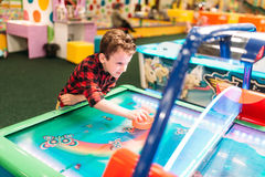 Active boy plays air hockey, entertainment center. Active boy plays air hockey in entertainment center. Happy childhood. Sport game attraction Royalty Free Stock Images