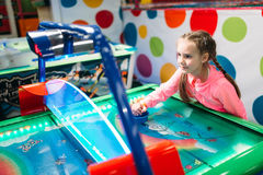 Active boy plays air hockey, entertainment center. Young girl plays air hockey in entertainment center. Happy childhood. Sport game attraction Stock Photos