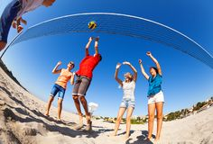 Active boys and girls playing volleyball on beach stock photo