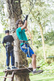 Active brave boy enjoying outbound climbing at adventure park on. Portrait of active brave boy enjoying outbound climbing at adventure park on tree top Royalty Free Stock Photography