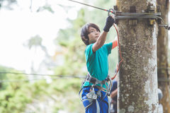 Active brave boy enjoying outbound climbing at adventure park on. Portrait of active brave boy enjoying outbound climbing at adventure park on tree top Stock Image