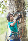Active brave boy enjoying outbound climbing at adventure park on. Portrait of active brave boy enjoying outbound climbing at adventure park on tree top Royalty Free Stock Photo