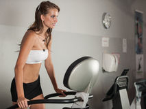 Active brunette - Beautiful slim girl work out on stepper in fit Royalty Free Stock Photo