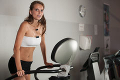Active brunette - Beautiful slim girl work out on stepper in fit Royalty Free Stock Image
