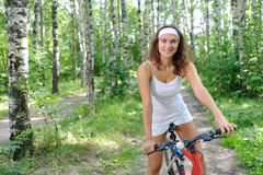 Active brunette woman on red bicycle Royalty Free Stock Photo