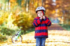 Active child putting safe helmet before cycling on sunny fall day in nature. Little kid boy in colorful warm clothes in autumn forest park with a bicycle stock photo