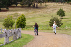 Active children. Two young girls cycling and skipping rope in the countryside Royalty Free Stock Images