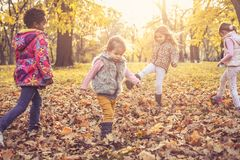 Active children playing in park. Four children enjoying in autumn day. Kids playing at park royalty free stock image
