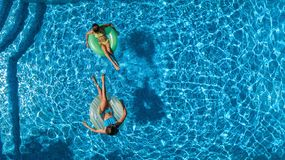 Active children in swimming pool aerial top view from above, happy kids swim on inflatable ring donuts and have fun in water. On family holiday vacation on stock photography