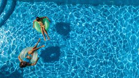 Active children in swimming pool aerial top view from above, happy kids swim on inflatable ring donuts and have fun in water. On family holiday vacation on stock images