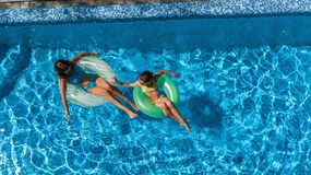 Active children in swimming pool aerial top view from above, happy kids swim on inflatable ring donuts and have fun in water. On family holiday vacation on stock image