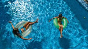Active children in swimming pool aerial top view from above, happy kids swim on inflatable ring donuts and have fun in water. On family holiday vacation on royalty free stock photo