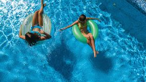 Active children in swimming pool aerial top view from above, happy kids swim on inflatable ring donuts and have fun in water. On family holiday vacation on royalty free stock photos