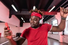 Active contented young man in red t-shirt having dancing music. Professional headphones. Active contented young man in red t-shirt having dancing music through stock image