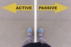 Active contra flechas pasivas del texto en la tierra, los pies y los zapatos del asfalto Imagen de archivo libre de regalías
