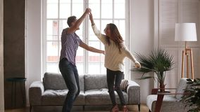 Active couple celebrate moving at new home dancing feels happy