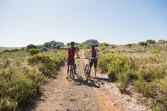 Active couple cycling in the countryside looking to the side Royalty Free Stock Photography