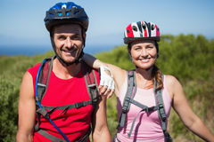 Active couple cycling in the countryside smiling at camera Royalty Free Stock Photography
