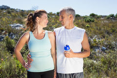 Active couple embracing each other on a jog in the country. On a sunny day Stock Photography