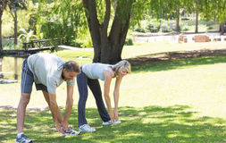 Active couple exercising in park Stock Photos