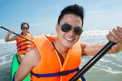 Active couple. Active happy couple kayaking in the sea royalty free stock photography