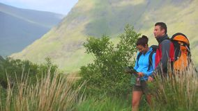 Active couple hiking together with map and pointing stock footage