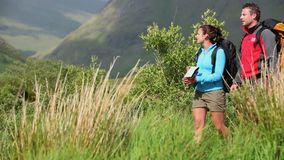 Active couple hiking together and reading map stock footage