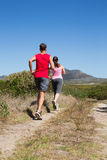 Active couple jogging on country terrain Stock Images