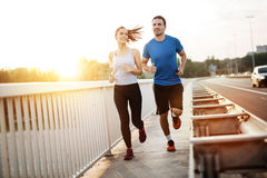 Active couple jogging. Outdoors during sunset royalty free stock image