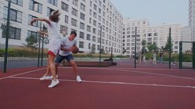 Active couple plays basketball or streetball on open stadium. Girl blocks and protect basket hoop. Man use stunt. Combination, jump and reaches the goal. Winner stock video footage