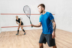 Active couple with rackets play squash game. In indoor training club. Recreation workout, match with racquet Royalty Free Stock Photo
