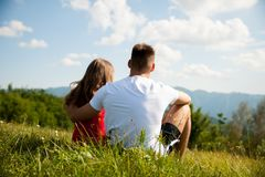 Active couple rests on a mountain peak looking on a mountain lan Stock Photo